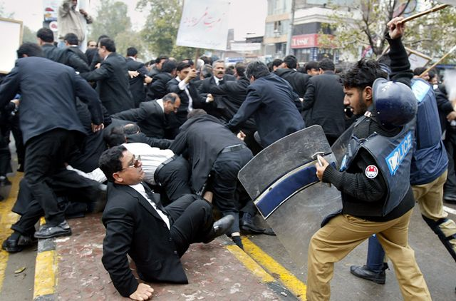 Pakistani police officers beat lawyers with batons during an anti-government rally in Lahore, Pakistan, Monday, March 12, 2007. Lawyers boycotted court proceedings, clashed with riot police, and burned an image of Pakistani President Gen. Pervez Musharraf in a countrywide protest against the ouster of the country's top judge. (AP Photo/K.M. Chaudary)