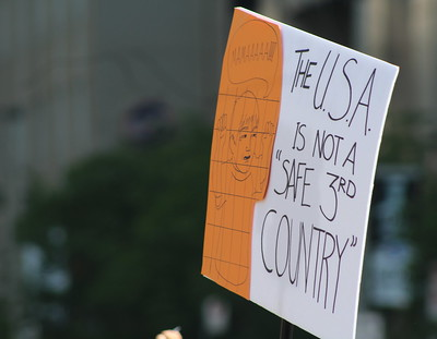 Image of a protest sign regarding the Canada-US Safe Third Country Agreement